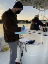 IEC staff entering data on a boat